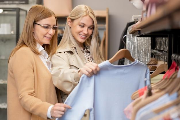 Счастливая молодая женщина показывает матери белый свитер, делая покупки в бутике или отделе одежды в торговом центре