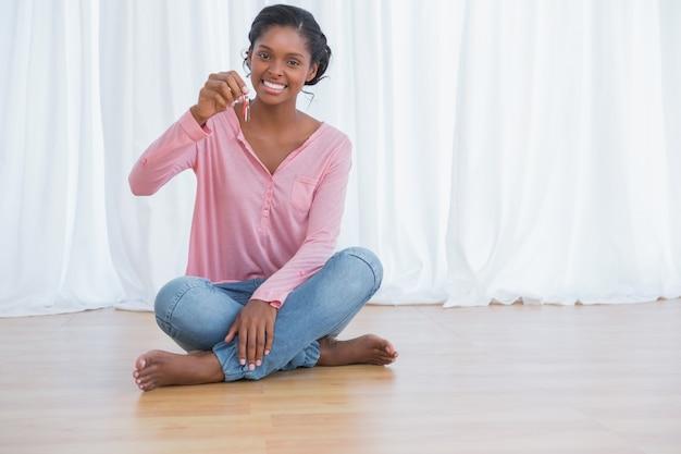 彼女の新しい家の鍵を見せている幸せな若い女性