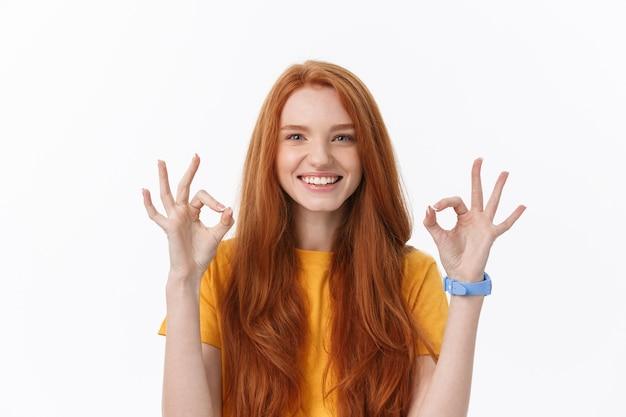 윙크하는 손가락으로 ok 사인을 보여주는 행복 한 젊은 여자