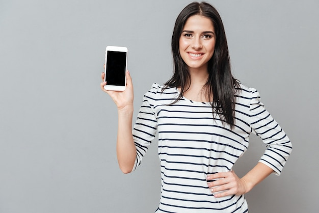 Happy young woman showing phone display to the front over grey surface. look at front.