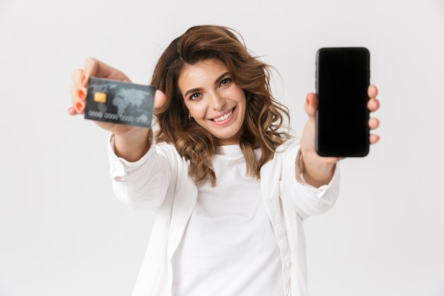 Happy young woman showing plastic credit card and blank screen mobile phone isolated