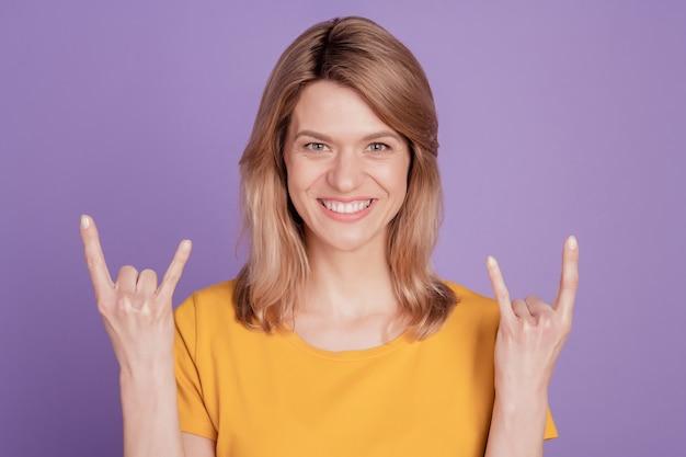 紫色の背景に分離されたロックジェスチャーを示し、楽しんで叫んで幸せな若い女性