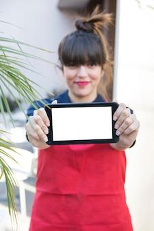 空の白い画面でスマートフォンを表示している幸せな若い女性