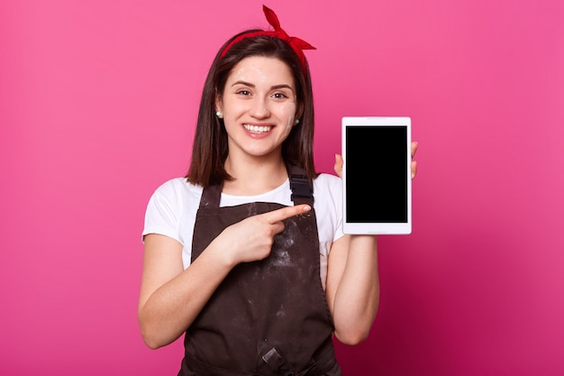 Happy young woman showing tablet computer screen, copy space for your advertisement or promotion text, isolated over pink wall, wears white t shirt, brown apron and red hair band