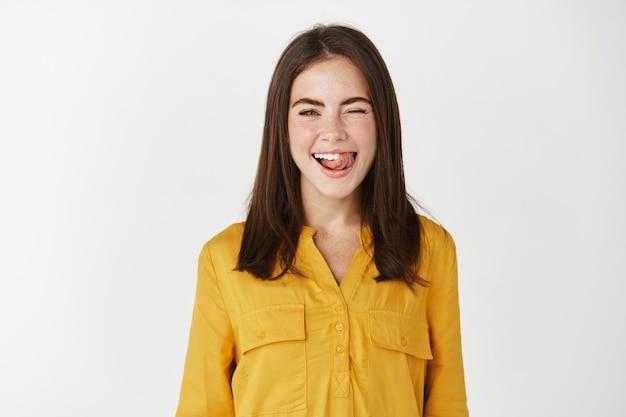 Счастливая молодая женщина показывает язык глупо и подмигивает в камеру, выражает позитив и радость, стоя в желтой блузке на белой стене