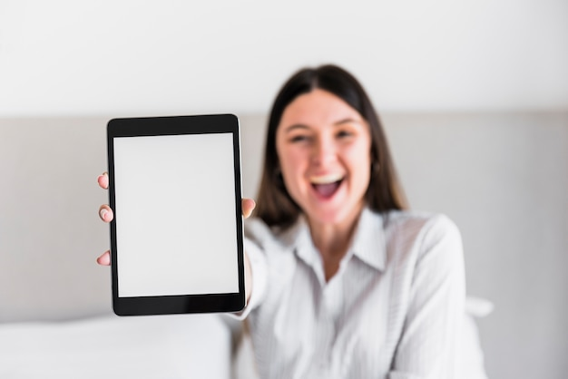 Happy young woman showing white screen digital tablet
