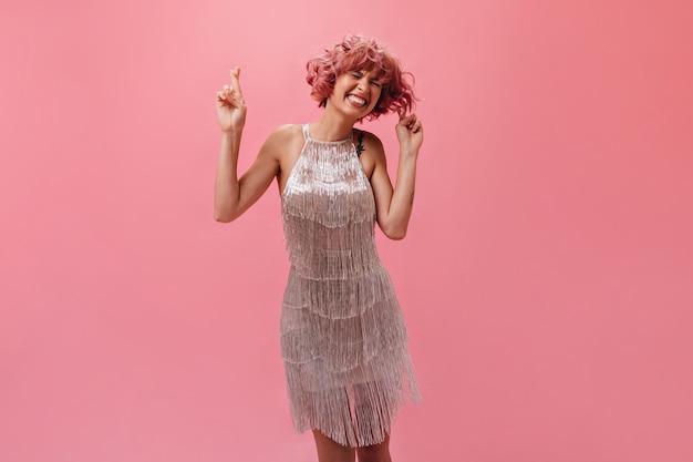 La giovane donna felice in vestito alla moda d'argento incrocia le dita