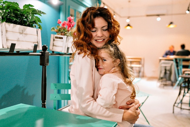 그녀의 매력적인 어린 소녀와 함께 카페에 앉아 그녀를 껴안고 행복 한 젊은 여자