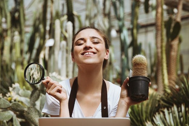 Happy young woman sitting in greenhouse using laptop