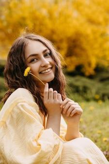 タンポポを保持している庭に座っている幸せな若い女性