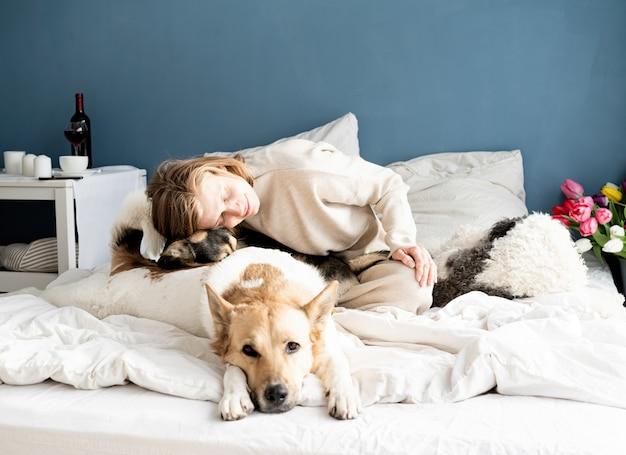 그녀의 강아지와 함께 침대에 앉아 행복 한 젊은 여자, 파란색 벽 배경