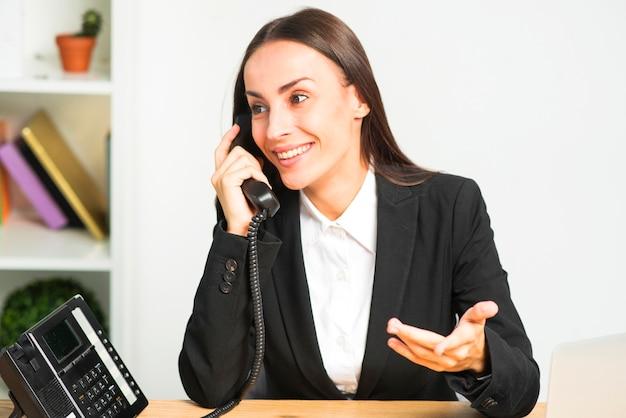 Счастливая молодая женщина, сидя в офисе, разговаривает по телефону жесты