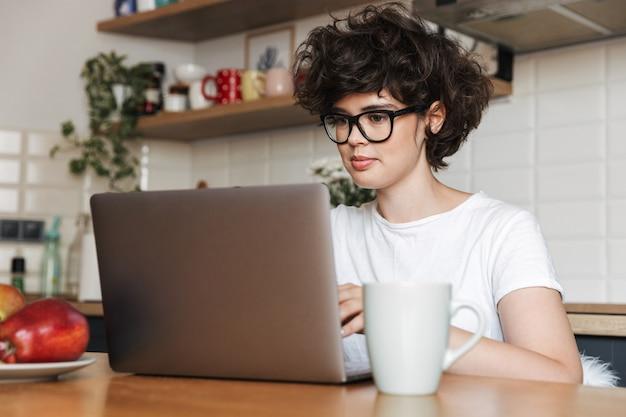 ラップトップコンピューターを使用してキッチンで屋内に座っている幸せな若い女性