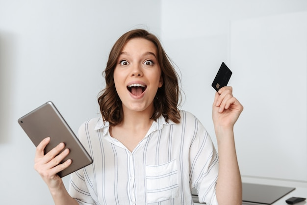 Happy young woman sitting at the kitchen at home, using tablet computer, holding credit card