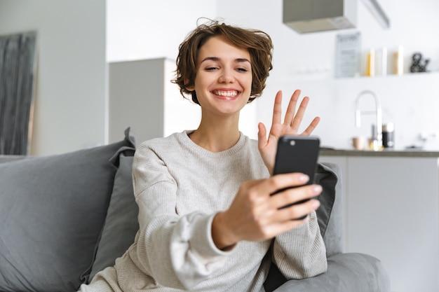 행복 한 젊은 여자 집에서 소파에 앉아 휴대 전화를 사용 하여 화상 통화를