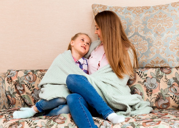 Счастливая молодая женщина, сидящая на уютном диване с очаровательной маленькой дочкой, завернутой в плед. мама и дочь веселятся в гостиной дома. концепция хороших семейных отношений.
