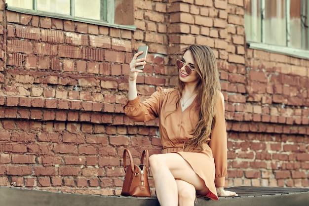 ベンチに座って、携帯電話でselfieを作る幸せな若い女