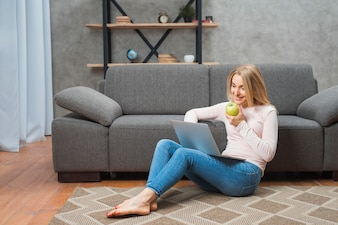 Happy young woman sitting on carpet holding green apple in hand using laptop