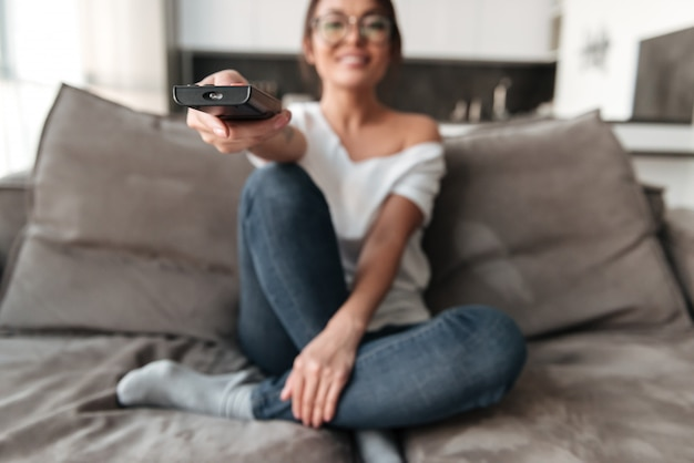 Счастливая молодая женщина, сидя на диване у себя дома смотреть телевизор.