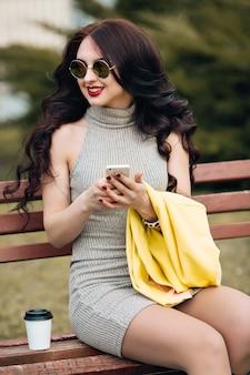 一杯のコーヒーと居心地の良い布でソファーに座っていた幸せな若い女。明るい黄色のファッションジャケット、灰色の春のドレス。