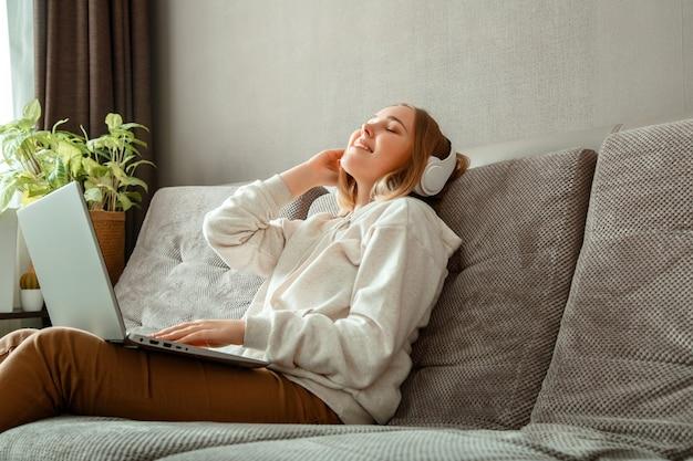 ラップトップを使用してヘッドフォンでソファに座って幸せな若い女性。休んでいる女性または10代の少女、至福は家のインテリアのソファで音楽を聴くことを楽しんでいます。目を閉じて休んでいる女性の肖像画。