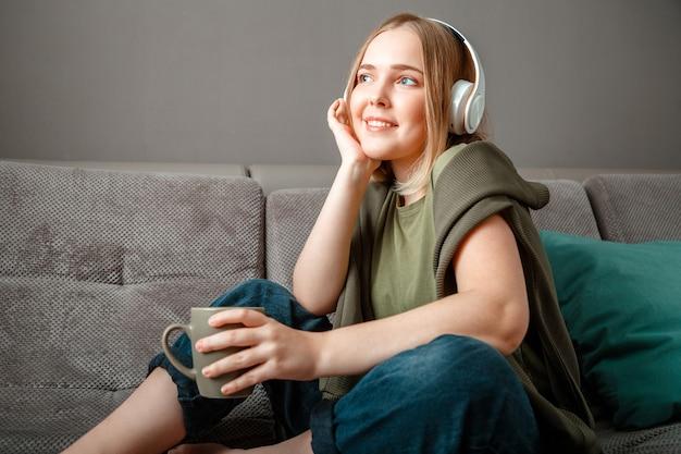 お茶とヘッドフォンでソファに座って幸せな若い女性。休んでいる女性または10代の少女、至福は居間の家の内部のソファで音楽を聴くことを楽しんでいます。