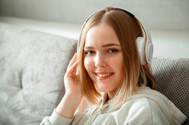 헤드폰에서 함께 소파에 앉아 행복 한 젊은 여자. 여자 또는 십 대 소녀 휴식, 행복은 거실의 홈 인테리어에서 소파에서 음악을 듣고 즐길 수 있습니다. 복사 공간을 쉬고 여자의 초상화입니다.