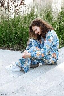 새로운 컬렉션 옷 카탈로그에서 포즈를 취하는 거리의 계단에 앉아 있는 행복한 젊은 여성