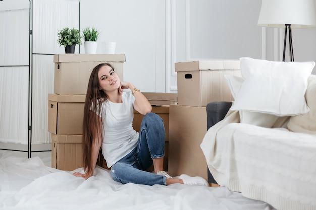 Счастливая молодая женщина, сидящая на полу в своей новой квартире