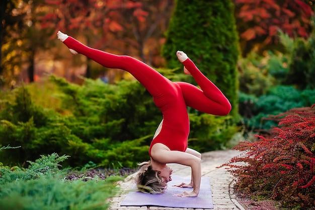 Счастливая молодая женщина, сидящая на открытом воздухе в позе йоги
