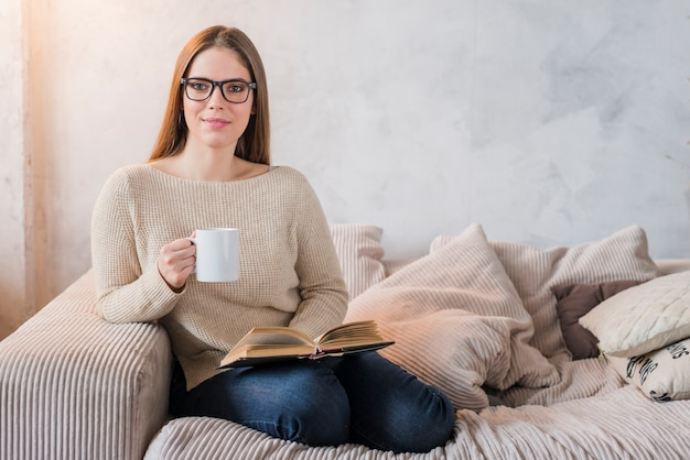 Happy young woman sitting on sofa holding book and cup of coffee in hands