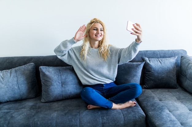 Happy young woman sitting on sofa with phone and having video call at home