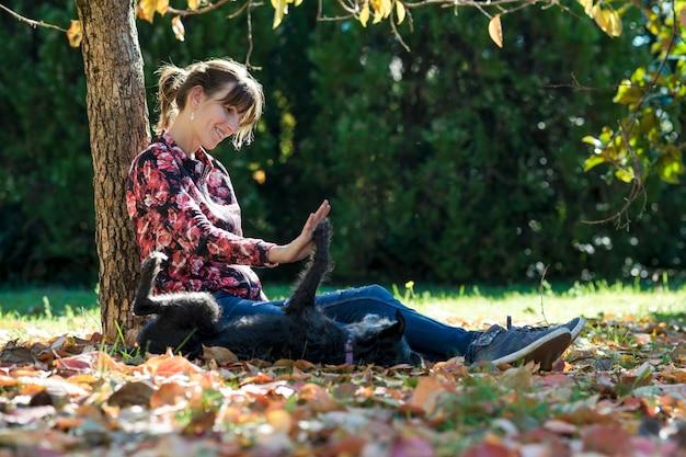 그녀의 검은 강아지와 함께 연주 공원에서 가을 나무 아래 앉아 행복 한 젊은 여자