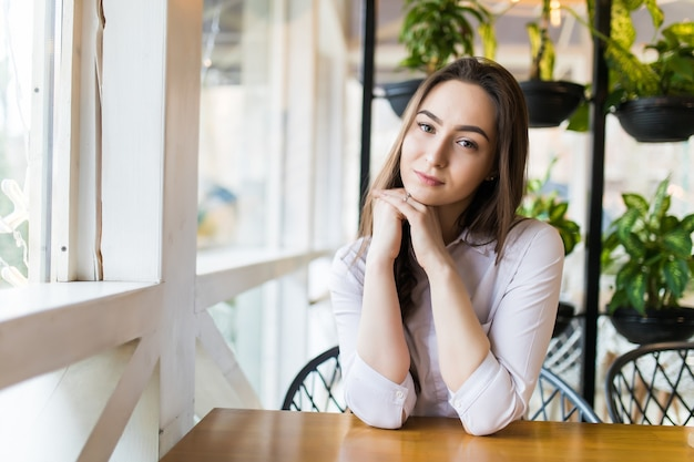 Felice giovane donna seduta e in attesa di ordine nella caffetteria