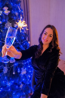Happy young woman sitting with glass of champagne and bengal light next to the christmas tree. new year party celebration. christmas winter holiday. new years eve.