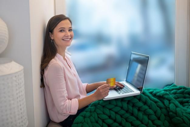 インターネットですべてを購入しながら彼女の銀行カードで座っている幸せな若い女性