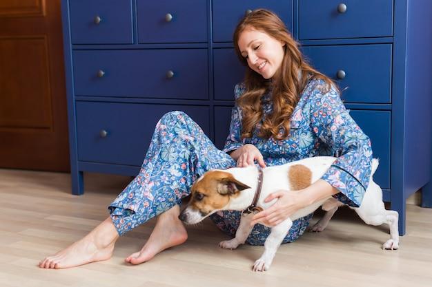 家で犬と一緒に座っている幸せな若い女性。