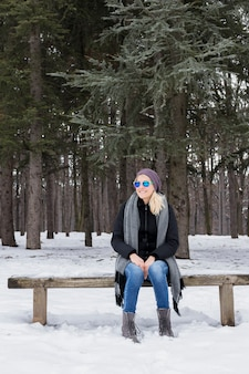 Happy young woman sitting on wooden bench wearing warm clothes in winter