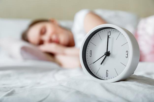 ベッドサイドの目覚まし時計の近くで寝ている幸せな若い女性。パジャマ姿の女性の穏やかな健康的な朝の睡眠。朝の日課と目覚まし時計から目を覚ます。 Premium写真