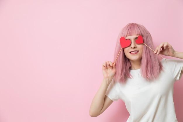 幸せな若い女性の笑顔と赤いハートを保持しています。バレンタインデーのコンセプト。