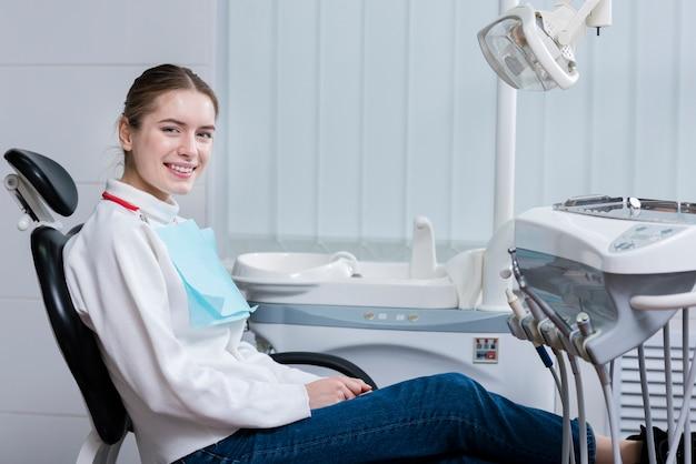Счастливая молодая женщина улыбается у стоматолога