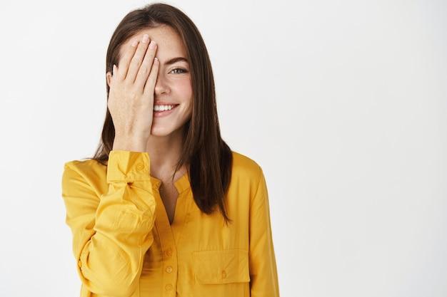 Felice giovane donna sorridente, nascondendo metà del viso dietro il palmo, mostrando un lato e fissando la telecamera, controllando la vista al negozio di ottica, in piedi vicino allo spazio della copia sul muro bianco.