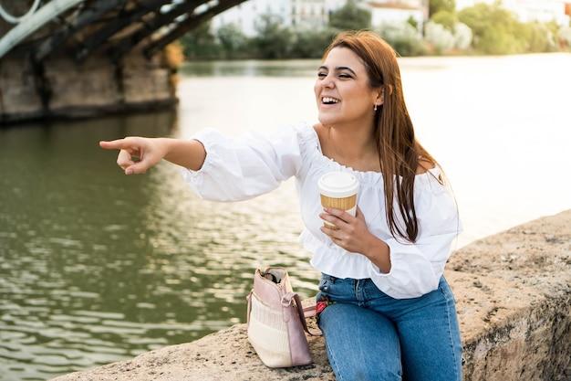 전망을 가리키며 웃고 강가에서 커피를 마시는 행복한 젊은 여성