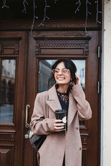 Happy young woman smiling in a trendy coat and sunglasses with a coffee walk in the city
