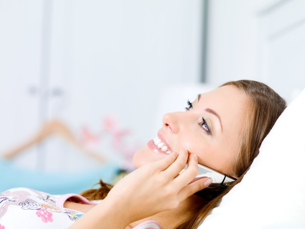 Happy young woman speaks on the phone lies on a bed