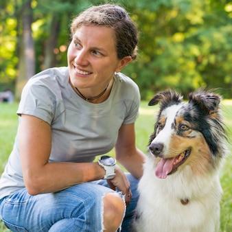Счастливая молодая женщина проводит время с прекрасной пятнистой австралийской овчаркой на зеленом лугу на