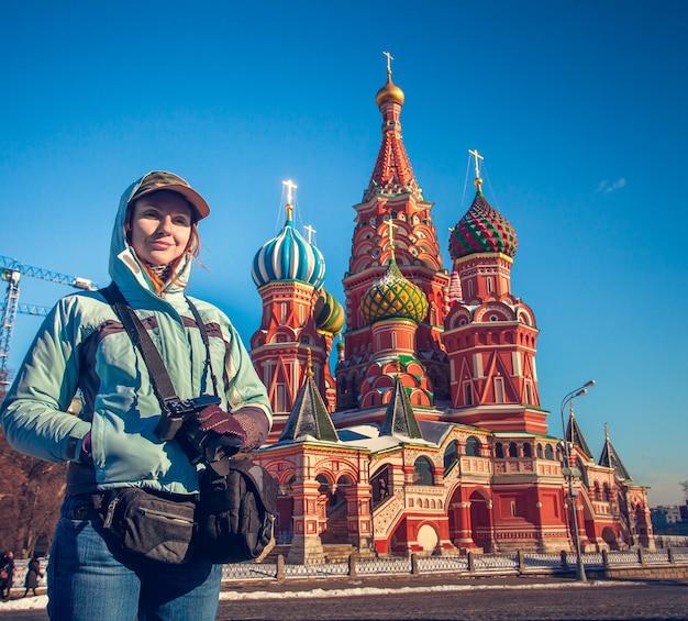Счастливая молодая женщина, противостоящая собору василия блаженного на красной площади в москве, россия. концепция путешествия. зимний сезон, яркие краски, ясное голубое небо.