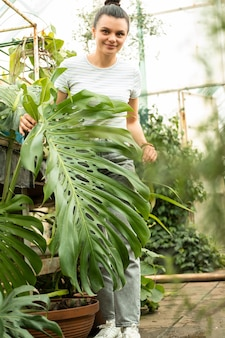 Happy young woman standing among monstera leaves in greenhouse, touching big green leaves, looking at camera.