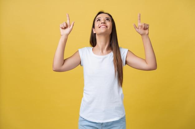 幸せな若い女性が立って、黄色い金色の壁の背景を探しているカメラの上に分離されたコピースペースに指を指しています。
