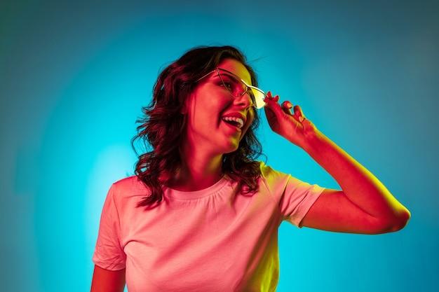 トレンディな青いネオンスタジオの上に立ってサングラスで笑って幸せな若い女性